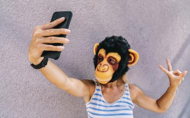 Crazy young woman with monkey mask stands on a gray wall and use a smartphone to take a selfie pic.- Stock Photo or Stock Video of rcfotostock | RC-Photo-Stock