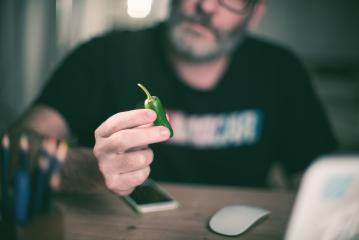 Creative designer looks at green pepper, hot chili pepper- Stock Photo or Stock Video of rcfotostock | RC-Photo-Stock