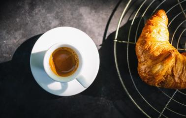Croissants with espresso. french croissants on bakery grid and cup of espresso coffee on dark concrete background, top view- Stock Photo or Stock Video of rcfotostock | RC-Photo-Stock