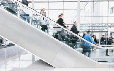 crowd of blurred people rushing on escalators at a trade fair hall- Stock Photo or Stock Video of rcfotostock | RC-Photo-Stock