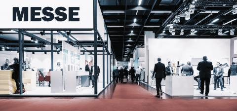 Crowd of people at a trade show booth with a banner and the german text Messe.- Stock Photo or Stock Video of rcfotostock   RC-Photo-Stock