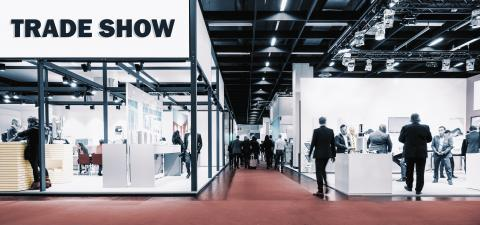 Crowd of people walking between trade show booths with a banner and the text Trade show.- Stock Photo or Stock Video of rcfotostock | RC-Photo-Stock