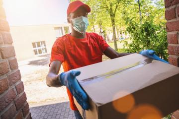 Delivery man employee in red cap blank t-shirt uniform face mask gloves hold empty cardboard box. Service quarantine pandemic coronavirus virus 2019-ncov concept image- Stock Photo or Stock Video of rcfotostock | RC-Photo-Stock
