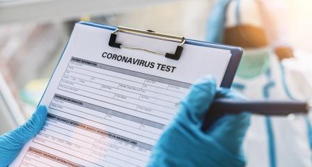 Doctor fills out a coronavirus test data sheet with pen for a patient in protective clothing in a clinic leaning at Covid-19 coronavirus epidemic- Stock Photo or Stock Video of rcfotostock | RC-Photo-Stock