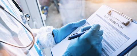 Doctor fills out a coronavirus test data sheet with pen in protective clothing in a clinic leaning against window at Covid-19 coronavirus epidemic- Stock Photo or Stock Video of rcfotostock   RC-Photo-Stock