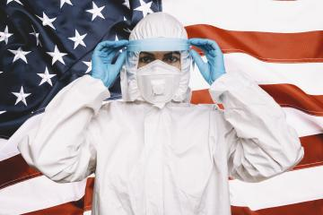 Doctor or Nurse Wearing Medical Personal Protective Equipment (PPE) with protective shield, Against The American Flag Banner. prevent corona COVID-19 and SARS infection concept image- Stock Photo or Stock Video of rcfotostock | RC-Photo-Stock