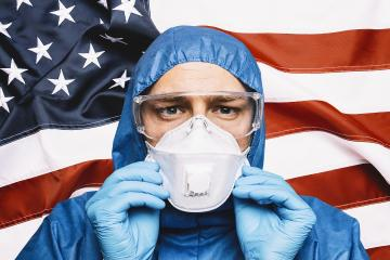 Doctor wearing protection Suit for Fighting Covid-19 (Corona virus) SARS infection Protective Equipment (PPE), Against The American Flag Banner. - Stock Photo or Stock Video of rcfotostock | RC-Photo-Stock