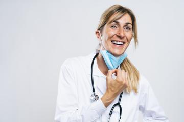 Female Doctor takes off N95 FFP2 an anti virus protection mask and is happy about it after corona COVID-19 and SARS cov 2 pandemic : Stock Photo or Stock Video Download rcfotostock photos, images and assets rcfotostock | RC-Photo-Stock.: