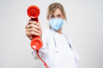 Female Doctor wearing N95 FFP2 an anti virus protection mask to prevent others from corona COVID-19 and SARS cov 2 infection and Holding Telephone Receiver : Stock Photo or Stock Video Download rcfotostock photos, images and assets rcfotostock | RC-Photo-Stock.: