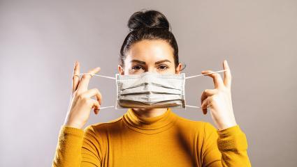 Frau hält Maske oder Mundschutz mit beiden Händen zum Thema Maskenpflicht und Abstandsregeln für 2G Regel und 3G Regel : Stock Photo or Stock Video Download rcfotostock photos, images and assets rcfotostock | RC-Photo-Stock.: