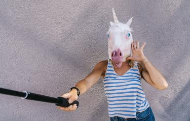 Freaky young woman in unicorn mask stands on a gray wall and use selfie stick to taking picture.- Stock Photo or Stock Video of rcfotostock | RC-Photo-Stock