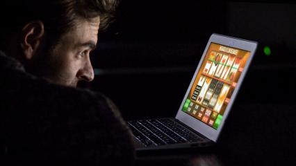 Gambling addicted man with glasses in front of online casino slot machine on laptop computer at night - loosing his money. Dramatic low light grain shot.- Stock Photo or Stock Video of rcfotostock | RC-Photo-Stock