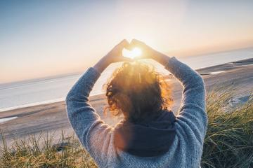 Girl holding a heart-shape with sunset light on the beach- Stock Photo or Stock Video of rcfotostock | RC-Photo-Stock