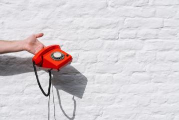 hand holding a Red telephone against a white brick wall- Stock Photo or Stock Video of rcfotostock | RC-Photo-Stock