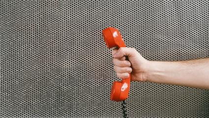 hand holding a red telephone receiver, office concept image- Stock Photo or Stock Video of rcfotostock | RC-Photo-Stock