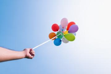 hand holding Colorful balloons against blue sky- Stock Photo or Stock Video of rcfotostock | RC-Photo-Stock