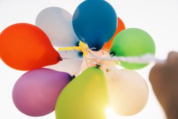 hand holding Colorful balloons against sun- Stock Photo or Stock Video of rcfotostock | RC-Photo-Stock