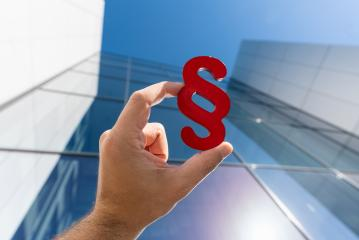 Hand holds paragraph sign to a lawyer office building- Stock Photo or Stock Video of rcfotostock   RC-Photo-Stock