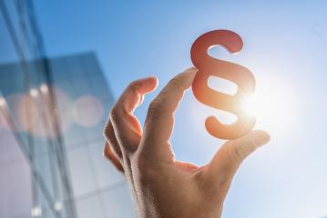 Hand holds paragraph symbol in the sun in to the sky with office building- Stock Photo or Stock Video of rcfotostock | RC-Photo-Stock
