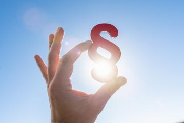 Hand holds paragraph symbol in the sun to the blue sky : Stock Photo or Stock Video Download rcfotostock photos, images and assets rcfotostock | RC-Photo-Stock.: