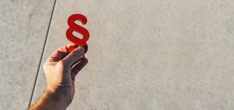 Hand holds red paragraphs as a sign of justice and Iustitia / Justitia the Roman goddess of Justice, banner size, copyspace for your individual text.- Stock Photo or Stock Video of rcfotostock | RC-Photo-Stock
