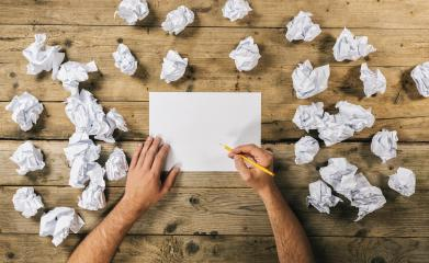 Hands holding blank paper sheet to write Mock-up or ideas with a pen surrounded from crumpled paper balls. Brainstorming Concept image : Stock Photo or Stock Video Download rcfotostock photos, images and assets rcfotostock | RC-Photo-Stock.: