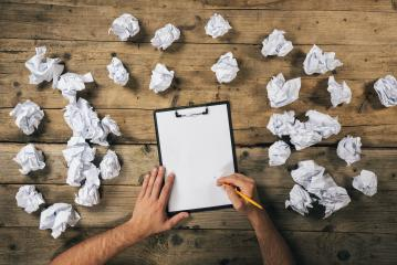 Hands holding clipboard and write Mock-up or ideas with a pen surrounded from crumpled paper balls. Brainstorming Concept image- Stock Photo or Stock Video of rcfotostock | RC-Photo-Stock