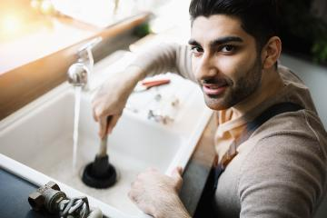 Handyman at work. Repairing kitchen sink by plunger. man trying to fix kitchen sink.- Stock Photo or Stock Video of rcfotostock | RC-Photo-Stock