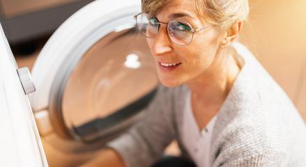 Happy Housewife at the washing machine or dryer in the kitchen room  : Stock Photo or Stock Video Download rcfotostock photos, images and assets rcfotostock | RC-Photo-Stock.: