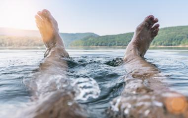 Happy man having fun and splashing water with his feet on a lake : Stock Photo or Stock Video Download rcfotostock photos, images and assets rcfotostock | RC-Photo-Stock.:
