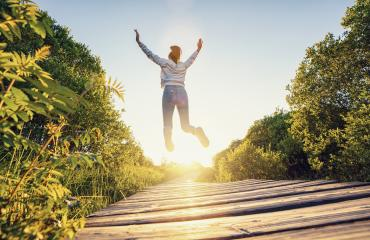 Happy woman jumping with raised hands and legs, and enjoying life over a Wooden path at sunset- Stock Photo or Stock Video of rcfotostock | RC-Photo-Stock