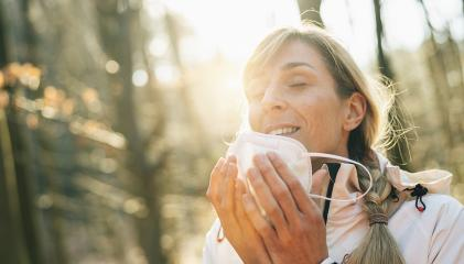 Happy woman removing medical knN95 FFP2 face mask while standing in forest during sunset. Woman removing protective face mask to take a deep breath during COVID-19 pandemic. Woman throwing away mask- Stock Photo or Stock Video of rcfotostock | RC-Photo-Stock
