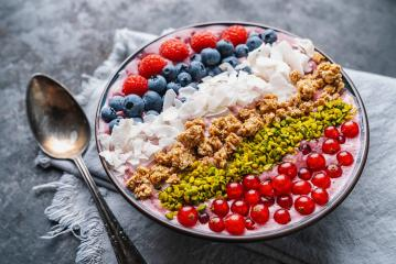 Healthy breakfast bowl, wirh blueberry smoothie with, raspberry, blueberrys, coconut, nuts and currants toppings on a table with spoon- Stock Photo or Stock Video of rcfotostock | RC-Photo-Stock