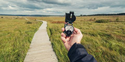 Hiker man searching direction with a compass in a bog landscape with wooden trail. View of hands. Point of view shot. : Stock Photo or Stock Video Download rcfotostock photos, images and assets rcfotostock | RC-Photo-Stock.: