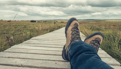 Hiking boots of a hiker while taking a rest on a wooden boardwalk, point of view. : Stock Photo or Stock Video Download rcfotostock photos, images and assets rcfotostock | RC-Photo-Stock.: