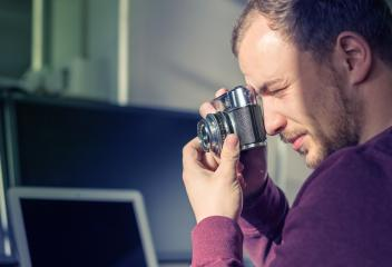 Hipster young man holding a vintage camera and taking a picture- Stock Photo or Stock Video of rcfotostock | RC-Photo-Stock