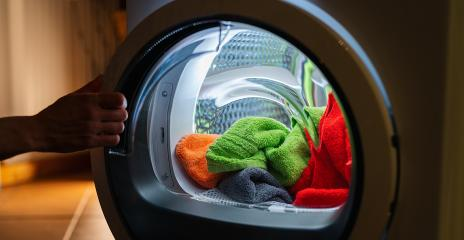 Housewife opens a  washing machine or dryer at night with many colorful clean fresh hand towels : Stock Photo or Stock Video Download rcfotostock photos, images and assets rcfotostock | RC-Photo-Stock.: