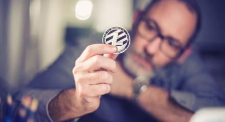 Litecoin cryptocurrency in hand of a casual businessman  : Stock Photo or Stock Video Download rcfotostock photos, images and assets rcfotostock | RC-Photo-Stock.: