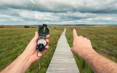 Male explorer searching direction with compass and shows the way in to the landscape, point of view.- Stock Photo or Stock Video of rcfotostock | RC-Photo-Stock