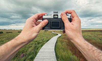 male hand holding a vintage camera against the a bog landscape with wooden boardwalk to take a picture, point of view perspective.- Stock Photo or Stock Video of rcfotostock | RC-Photo-Stock
