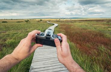 male hand holding a vintage camera against the a landscape with boardwalk to take a picture, pov, point of view perspective.- Stock Photo or Stock Video of rcfotostock | RC-Photo-Stock