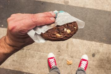 Male person standing on the street with fresh Chocolate Cookie in his hand. First person POV. Top view.- Stock Photo or Stock Video of rcfotostock | RC-Photo-Stock