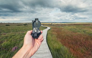 Male traveler holds a compass on background of a bog landscape with wooden trail and cloudy sky, view of hand, pov.- Stock Photo or Stock Video of rcfotostock | RC-Photo-Stock
