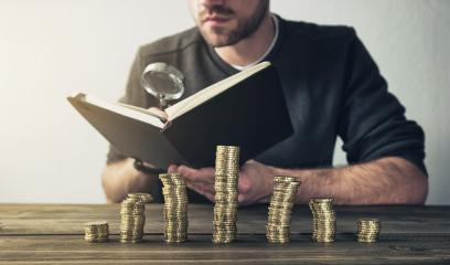 Man Checking Finances using magnifying glass with coins on stacks- Stock Photo or Stock Video of rcfotostock   RC-Photo-Stock