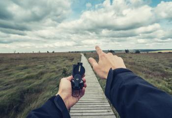 Man explorer searching direction with compass at a cloud day in the  high Venn (Hautes fagnes), point of view.- Stock Photo or Stock Video of rcfotostock | RC-Photo-Stock