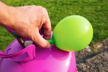 man filling green balloon with helium gas- Stock Photo or Stock Video of rcfotostock | RC-Photo-Stock
