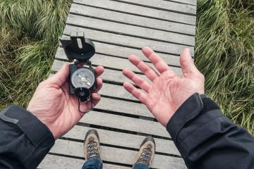 Man hold a compass and searching direction the direction on a wooden boardwalk, point of view. : Stock Photo or Stock Video Download rcfotostock photos, images and assets rcfotostock | RC-Photo-Stock.: