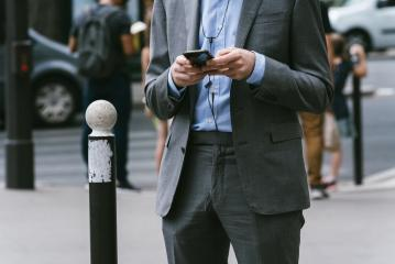 man outdoors using a smpartphone with a cable plugged into it- Stock Photo or Stock Video of rcfotostock | RC-Photo-Stock