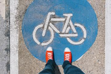 Man standing on bicycle zone sign on a asphalt city street in red sneakers, point of view perspective : Stock Photo or Stock Video Download rcfotostock photos, images and assets rcfotostock | RC-Photo-Stock.: