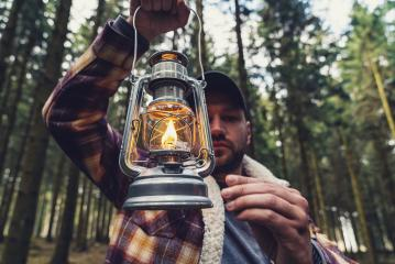 Man using a Gasoline lamp in the deep forest at autumn- Stock Photo or Stock Video of rcfotostock | RC-Photo-Stock
